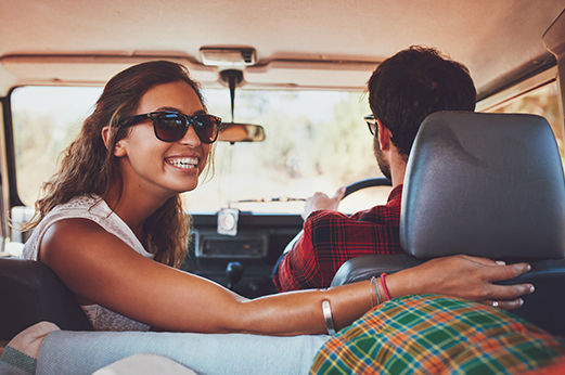 Excited couple with bright smiles, headed on a road trip.